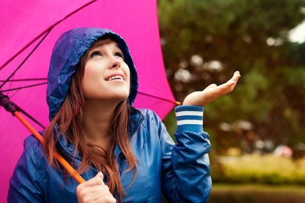 Schöne junge frau im regenmantel mit regenschirm, der für regen prüft