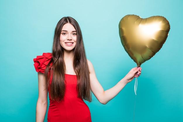 Schöne junge frau im roten kleid mit herzform-luftballon. frau am valentinstag. symbol der liebe