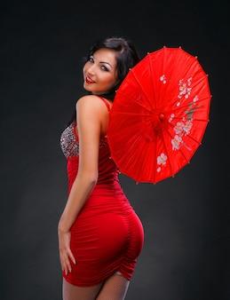 Schöne junge frau im roten kleid mit rotem chinesischem regenschirm auf dunklem hintergrund