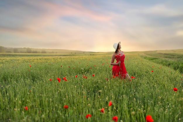 Schöne junge frau im roten kleid und im weißen hut geht um feld mit mohnblumen in einem schönen summ