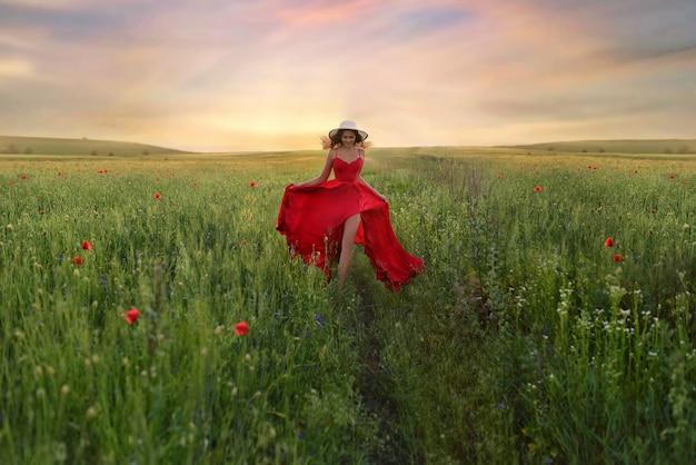 Schöne junge frau im roten kleid und im weißen hut geht um feld mit mohnblumen