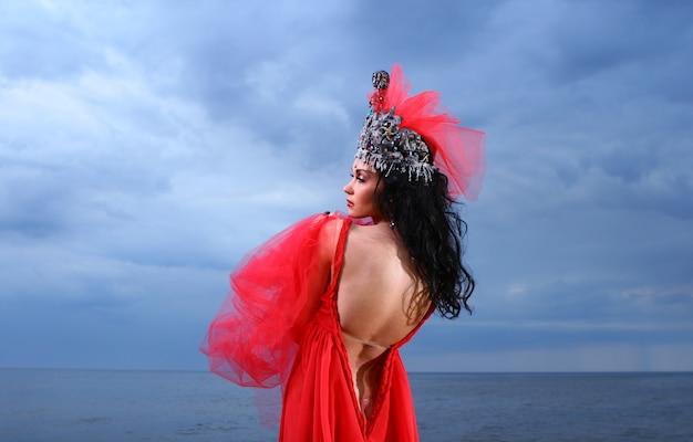 Schöne junge frau im roten langen kleid nahe dem meer