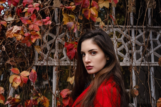 Schöne junge frau im roten mantel genießt herbstpark. ein angenehmer spaziergang auf dem hintergrund eines zauns mit zweigen wilder trauben und roten blättern
