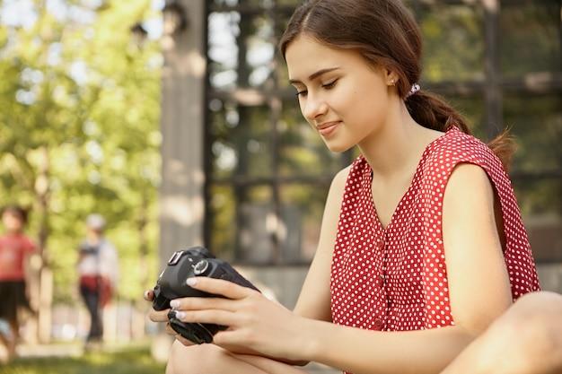 Schöne junge frau im roten polka-kleid, das draußen mit dslr-kamera sitzt und lernt, wie man professionelle fotos macht, bilder scrollt und anzeige betrachtet
