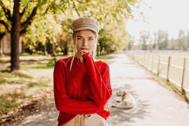 Schöne junge frau im roten pullover und im schönen trendigen hut, der im herbstpark nachdenklich aussieht. attraktive blondine in stilvoller kleidung, die im freien aufwirft.