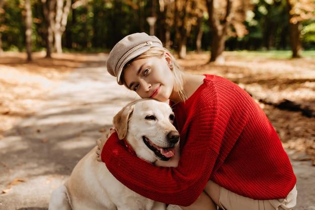 Schöne junge frau im schönen hellen hut und im roten pullover, die zusammen mit labrador im herbstpark sitzen. hübsche blondine und ihr hund sitzen zwischen laub.