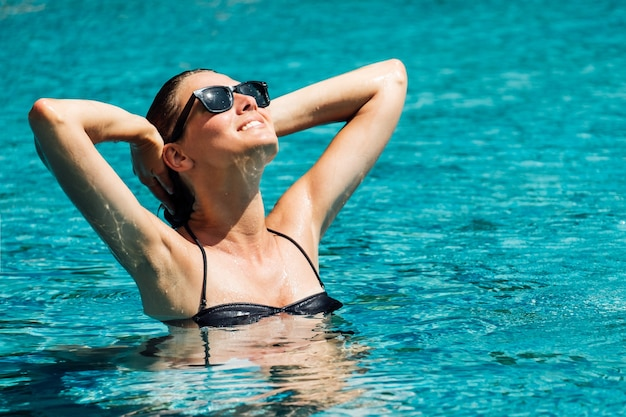 Schöne junge frau im schwarzen bikini, der im hotelpool entspannt. sorglose zeit am pool