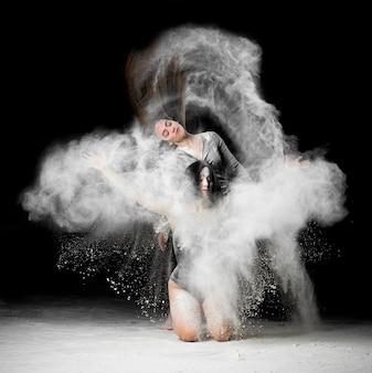 Schöne junge frau im schwarzen bodysuit, der in einer weißen mehlwolke tanzt