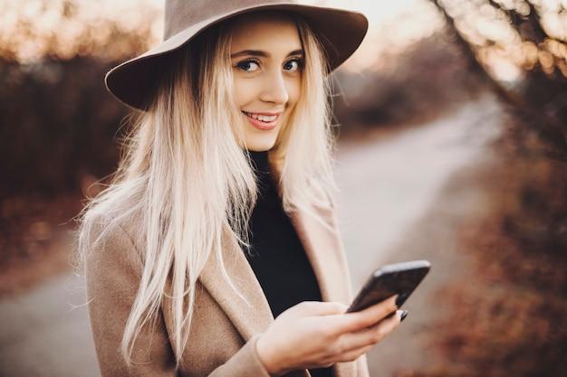 Schöne junge frau im stilvollen hut, der lächelt und kamera betrachtet, während sie smartphone durchsucht und auf unscharfem hintergrund der herbstlandschaft steht. lächelnde frau, die smartphone in der landschaft verwendet