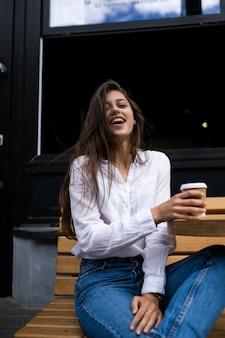 Schöne junge frau im straßencafé trinkt kaffee, im freien