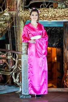 Schöne junge frau im traditionellen orientalischen kimonokleid anlässlich der chinesischen neujahrsfeier
