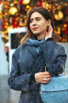 Schöne junge frau im trendigen mantel, die während des schneefalls auf der straße spazieren geht