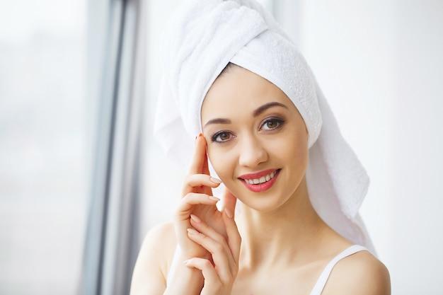 Schöne junge frau im tuch ganz bereit, badekur zu erhalten