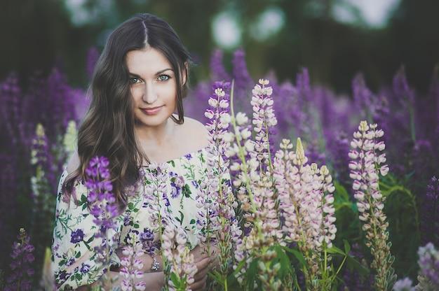 Schöne junge frau im ultravioletten und weißen kleid, die einen blumenstrauß von lupine bei sonnenuntergang auf dem feld hält. das konzept von natur und romantik. das tonen