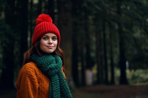Schöne junge frau im wald in hellen kleidern, einem roten hut, einem orangefarbenen pullover, in einem grünen schal reist, wandert in der natur im wald