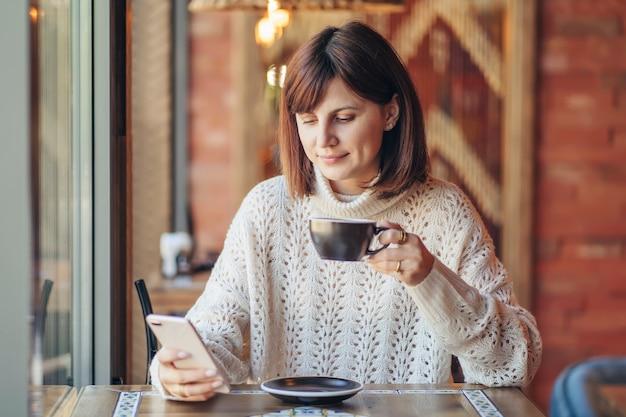 Schöne junge frau im warmen pullover mit smartphone im café am fenster mit kaffee. gemütlicher herbst- oder wintermorgen.