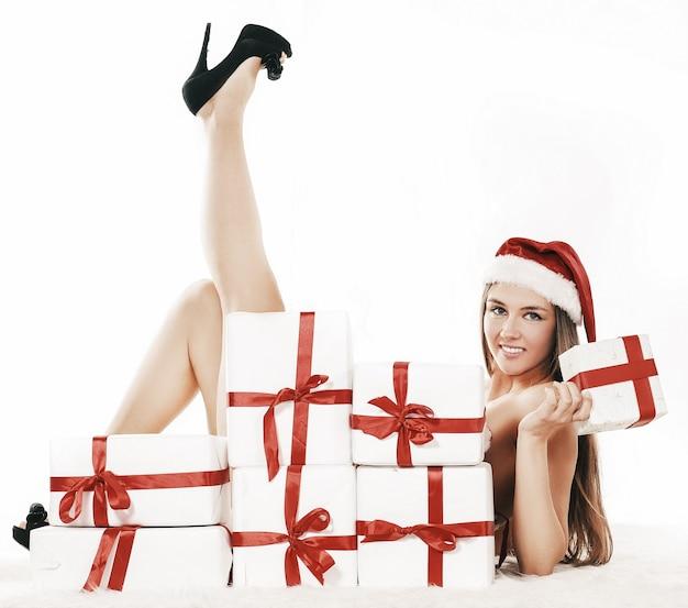 Schöne junge frau im weihnachtskostüm, das nahe dem stapel der weihnachtsgeschenke liegt