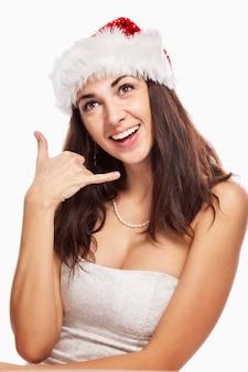 Schöne junge frau im weihnachtsmann-hut lacht. vertikale. isoliert weiß