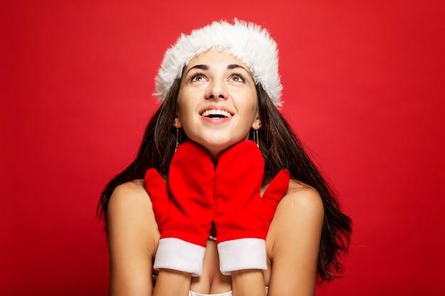 Schöne junge frau im weihnachtsmann-hut- und -handschuhlächeln. weihnachtsgeschichte. postkarte. copyspace. rot .