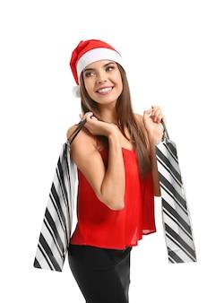 Schöne junge frau im weihnachtsmann-hut und mit taschen auf weißem hintergrund. weihnachtseinkaufskonzept