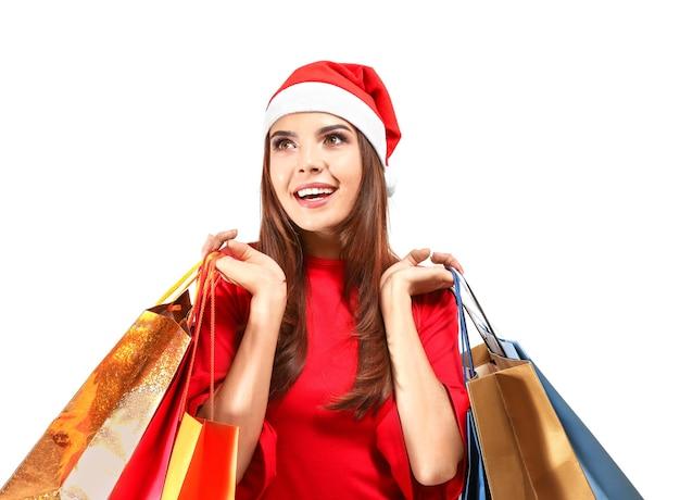 Schöne junge frau im weihnachtsmann-hut und mit taschen auf weißer oberfläche. weihnachtseinkaufskonzept