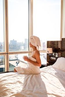 Schöne junge frau im weißen badtuch auf dem kopf, der nach dusche auf bett mit tasse kaffee sich entspannt