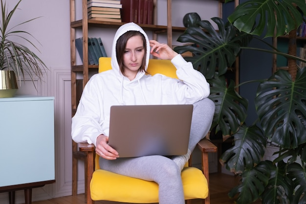 Schöne junge frau im weißen kapuzenpulli mit laptop, der auf gelbem sessel zu hause sitzt