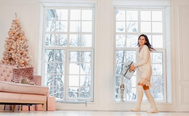 Schöne junge frau im weißen kleid, das mit geschenkbox aufwirft