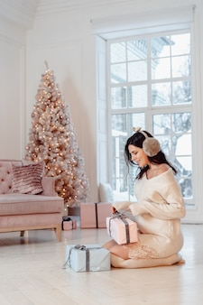 Schöne junge frau im weißen kleid, das mit geschenkboxen aufwirft