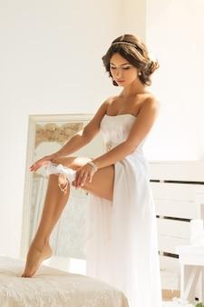 Schöne junge frau im weißen kleid, das sich zum hochzeitstag vorbereitet und strumpfband auf ihr bein setzt. details zum morgen der braut.