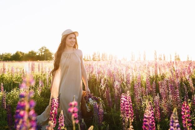 Schöne junge frau im weißen kleid und im strohhut, die in blumenfeld gehen