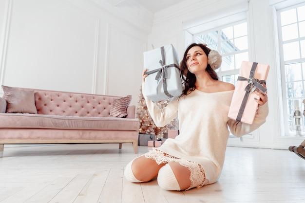 Schöne junge frau im weißen kleid. weihnachtskonzept