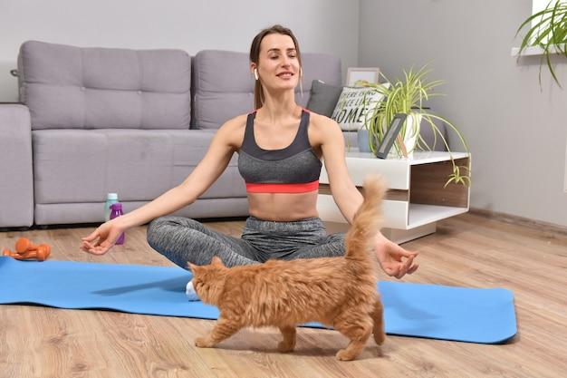 Schöne junge frau im yoga, das mit der roten katze innen in der wohnung aufwirft.
