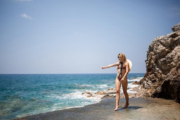 Schöne junge frau in braunem badeanzug und hut geht am strand am meer entlang