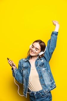 Schöne junge frau in den kopfhörern, die musik hören und auf gelber wand tanzen