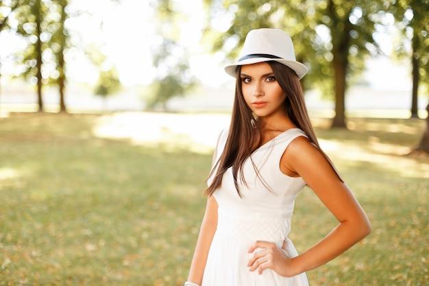Schöne junge frau in den weißen kleidern mit hut, der draußen an einem sommertag aufwirft