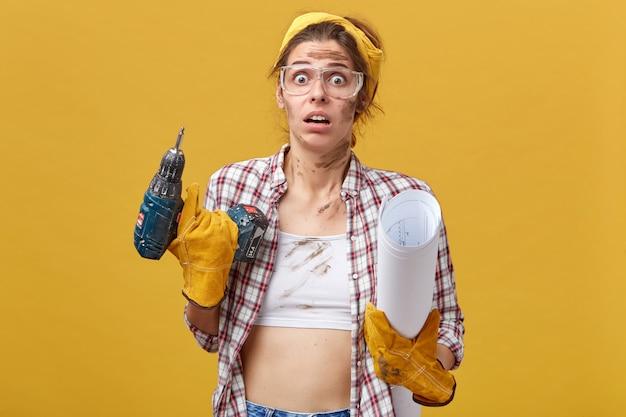 Schöne junge frau in der arbeitskleidung, die bohrer und blaupause hält, erschrockenes aussehen erkennt, dass sie selbst arbeiten sollte, ohne hilfe ihres mannes, der nicht weiß, womit er anfangen soll