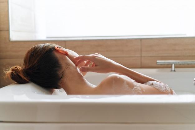 Schöne junge frau in der badewanne