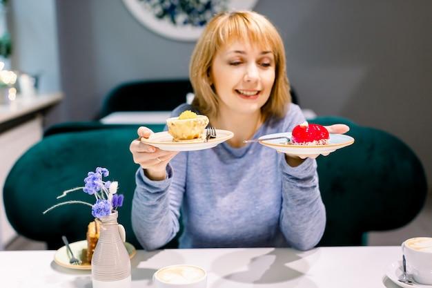 Schöne junge frau in der blauen strickjacke trinkt tee und kuchen in einem netten café. frau, die zwischen den roten und gelben geschmackvollen nachtischen wählt