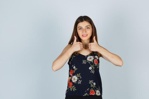 Schöne junge frau in der bluse, die doppelte daumen oben zeigt und glücklich schaut