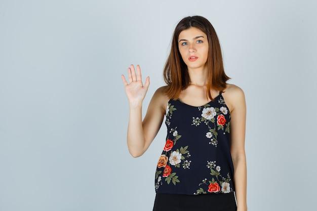 Schöne junge frau in der bluse, die hand für begrüßung und selbstbewusstsein winkt