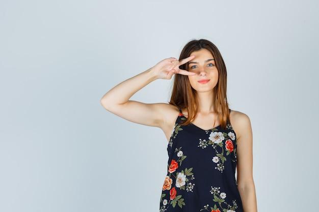 Schöne junge frau in der bluse, die v-zeichen nahe auge zeigt und fröhlich schaut