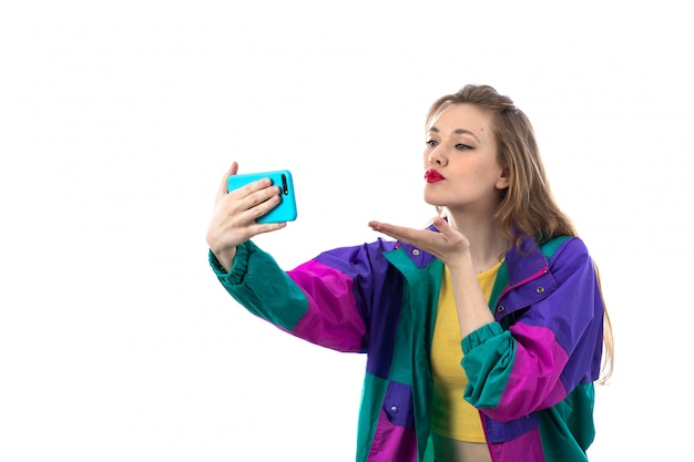 Schöne junge frau in der bunten jacke mit smartphone für selfie-foto