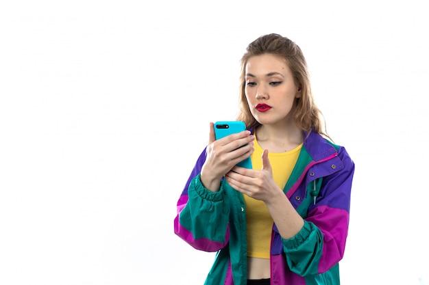 Schöne junge frau in der bunten jacke und im halten des smartphones