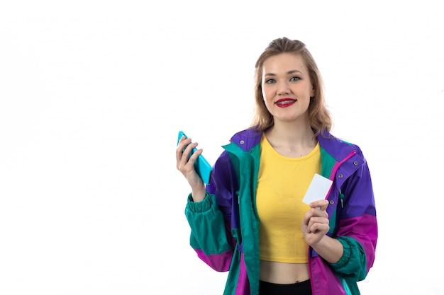 Schöne junge frau in der bunten jacke unter verwendung des smartphones und der kreditkarte