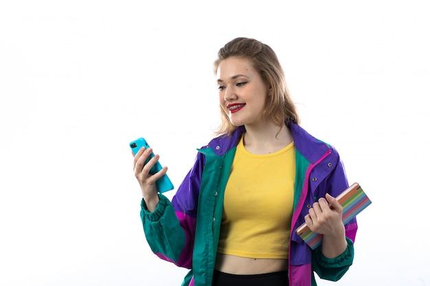 Schöne junge frau in der bunten jacke unter verwendung des smartphones und des haltebuchs