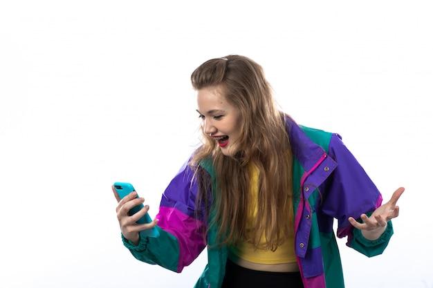 Schöne junge frau in der bunten jacke unter verwendung des smartphones