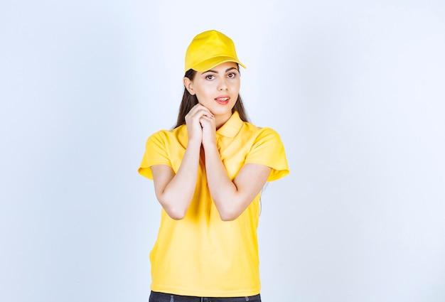 Schöne junge frau in der gelben ausstattung, die auf weiß steht und schaut.
