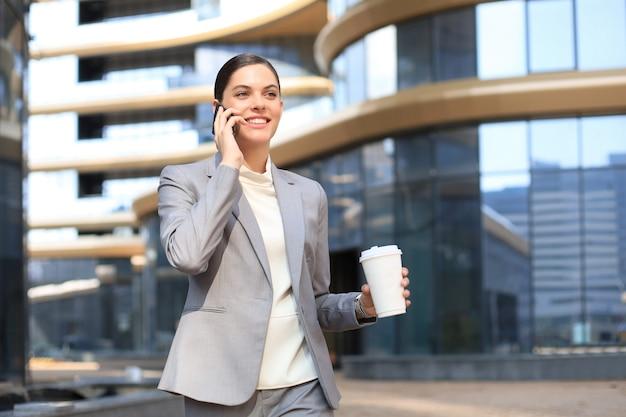 Schöne junge frau in der klage, die intelligentes telefon verwendet und lächelt, während sie draußen steht.