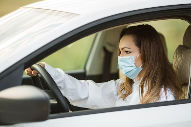 Schöne junge frau in der medizinischen maske, die ein auto fährt